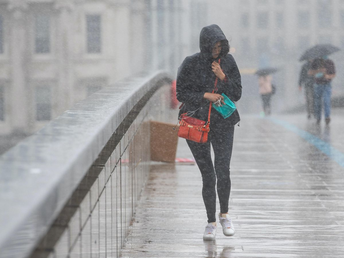 A woman runs to take shelter from a heavy downpour of rain on London Bridge