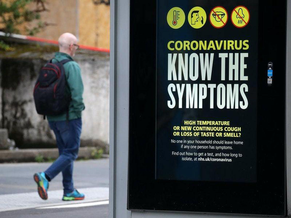 Man walks past coronavirus sign