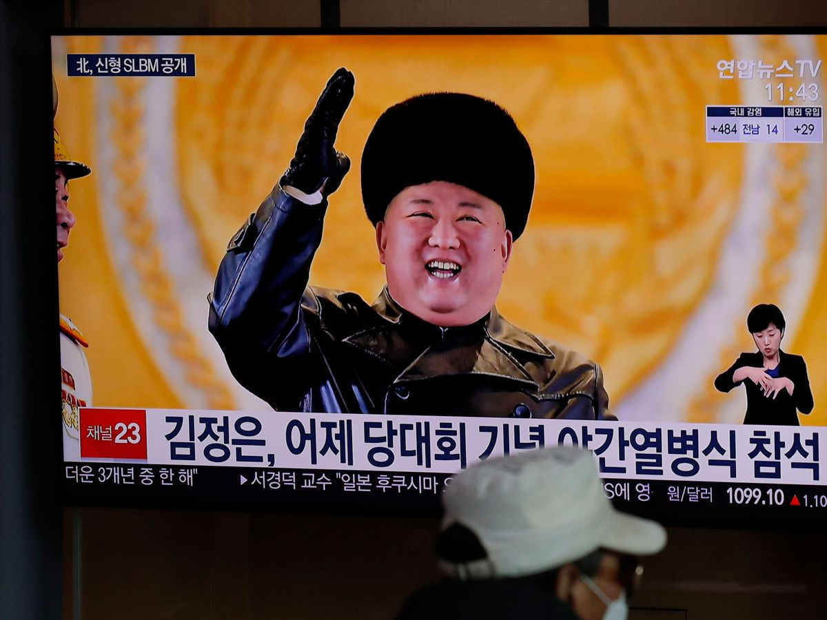 A man wearing a face mask sits in front of a TV screen showing North Korean leader Kim Jong Un (Lee Jin-man/AP)