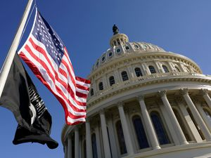Flags fly on the US Capitol in Washington ahead of the 59th Presidential Inauguration