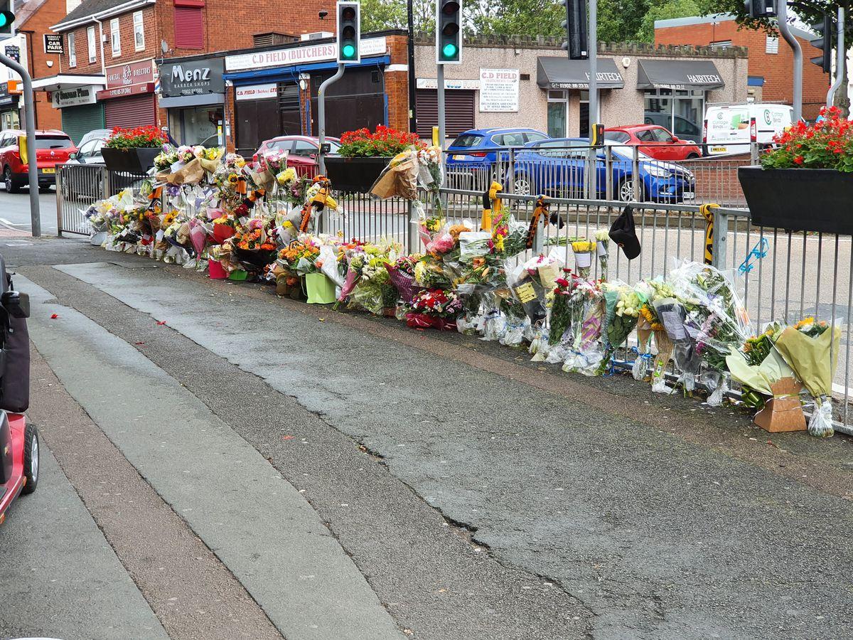 The tributes run along the railings outside The Clifton pub