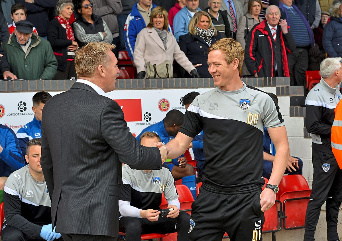 Dean Smith shakes Dean Holden's hand at the start of the match.