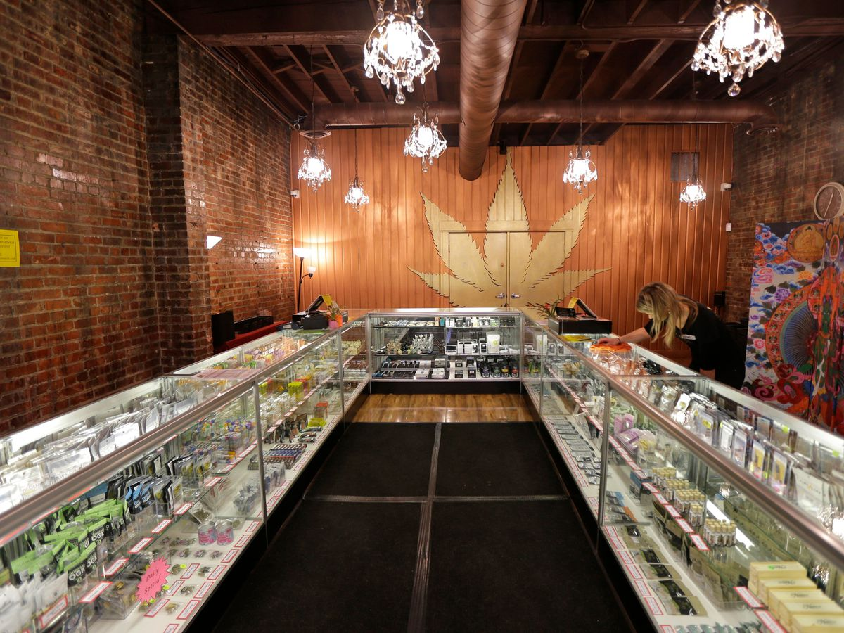 A worker cleans a display case at the Ganja Goddess Cannabis Store in Seattle