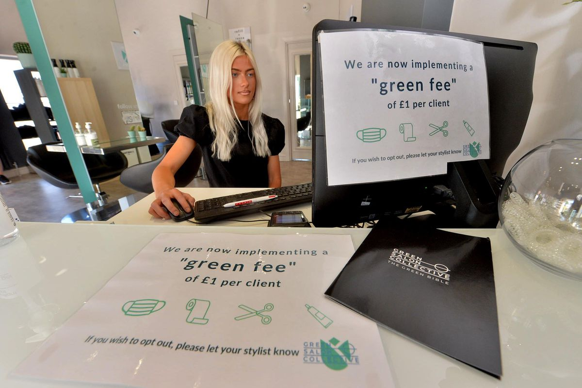 Charlie Mullett with the signs showing there is a £1 green fee, which customers can opt out of