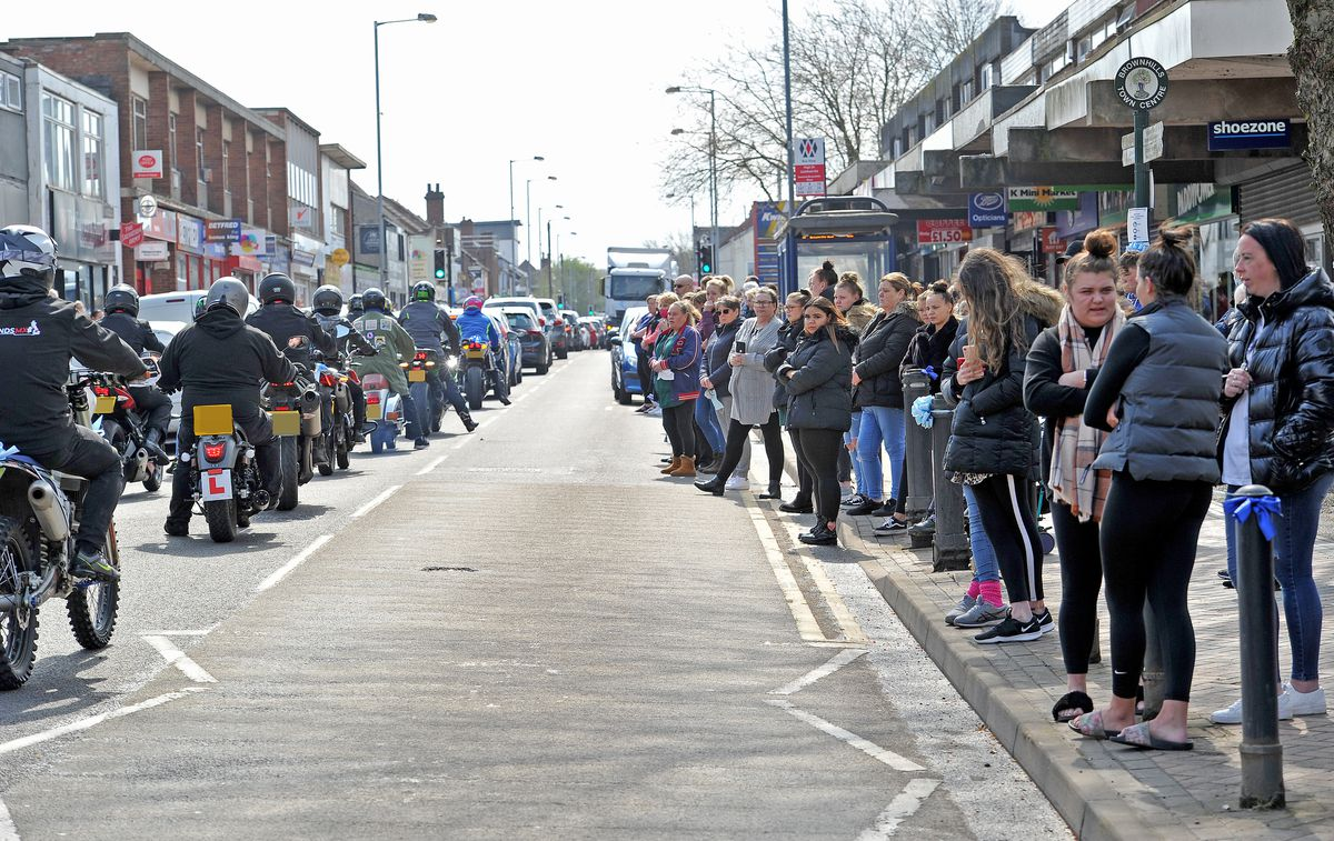 Motorcylists bearing blue ribbons accompany the funeral procession