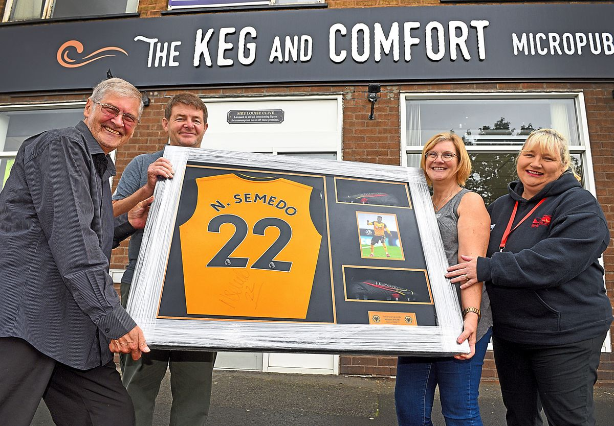 WOLVERHAMPTON COPYRIGHT MNA MEDIA TIM THURSFIELD 15/08/21 .Keg & Comfort, Wolverhampton, has been raising funds for the Midlands Air Ambulance charity both during the lockdown and recently with various raffles and sweepstakes..Their most recent one has been for a Nelson Semedo, WWFC player, framed shirt and boots set to be auctioned off..Pictured is winner Paul Waddell(left) with John and Louise Clive from the Keg and Comfort, and Jo Bailey from Midlands Air Ambulance....