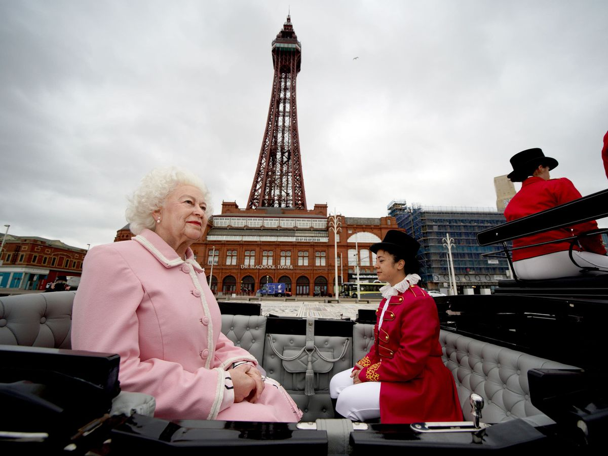 The wax figure of the Queen passes Blackpool Tower in a horse-drawn carriage