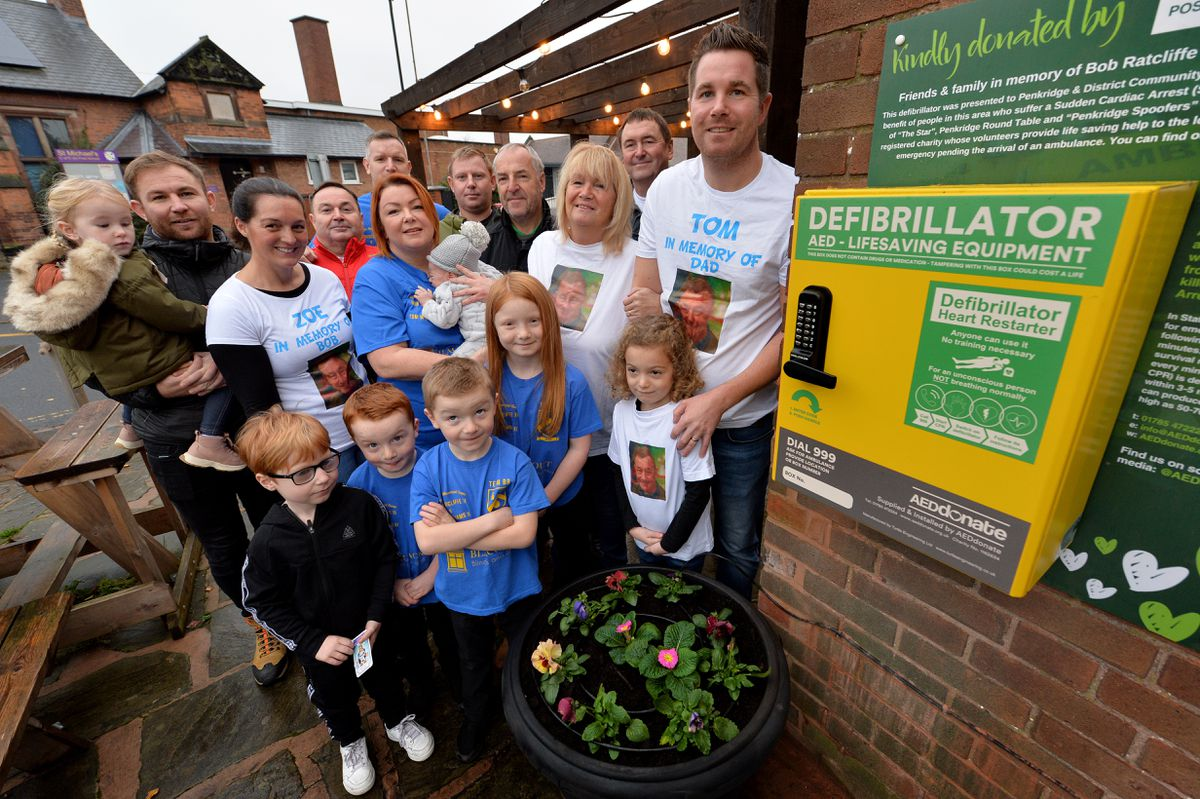 Tom Ratcliffe and his family and friends pose next to a defibrillator, one of three installed in Penkridge