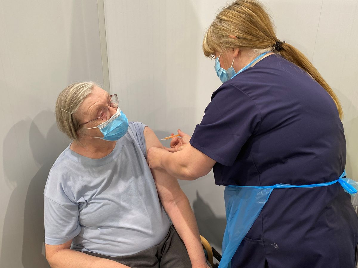 Christine Adams, 74, from Tipton, receives her vaccine from consultant nurse Michelle Dexter at Tipton Sports Academy. Photo: Sandwell and West Birmingham Clinical Commissioning Group.