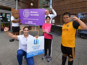 Donating laptops at St Luke's CE Primary School, Wolverhampton, is Wolfie, UNITED SIKHS director Sun Kaur, and Pat McFadden MP, with pupils Skye Kumari, aged 10, and Taranveer Saund, aged nine
