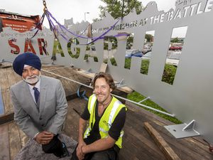 Councillor Bhupinder Gakhal (cabinet member for city assets and housing) and sculpter Luke Perry prepare to install the back plate for the Battle of Saragarhi Statute
