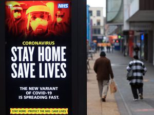 People pass a Stay Home, Save Lives sign