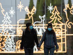 A couple walks amongst festive lighting by the Bullring shopping centre in Birmingham