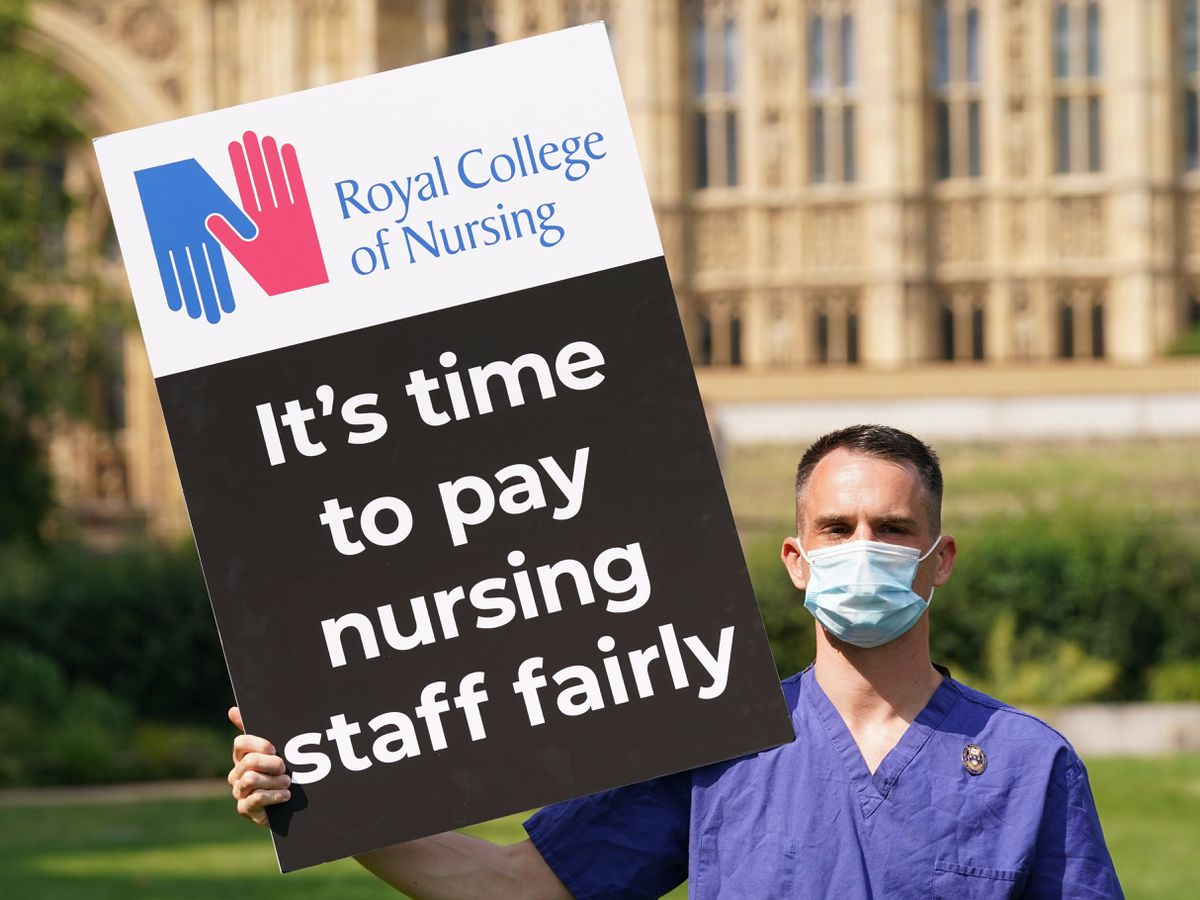 A Nurse with a placard outside the Royal College of Nursing (RCN) in Victoria Tower Gardens, London
