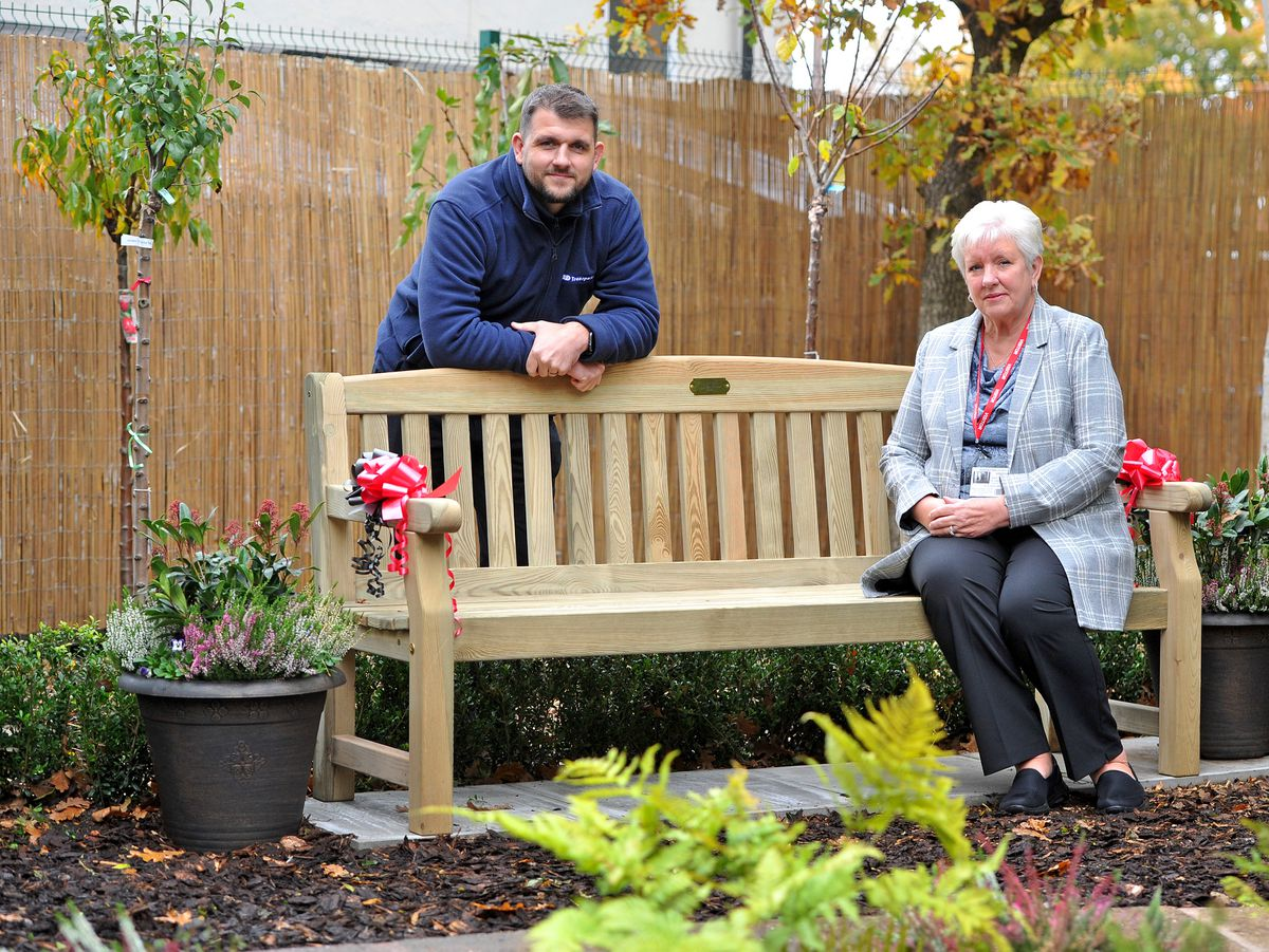 SANDWELL COPYRIGHT EXPRESS&STAR TIM THURSFIELD-16/10/20.Holyhead Primary Academy, in Wednesbury, has built a memorial garden in honour of former governor Steve Dale, who was highly influential in Wednesbury. Was also part of the town's Rotary club, rugby club and ran a successful business. Pictured with the memorial bench are Steve Dale's widow Lesley and son Matt with the new memorial bench at Holyhead Primary Academy