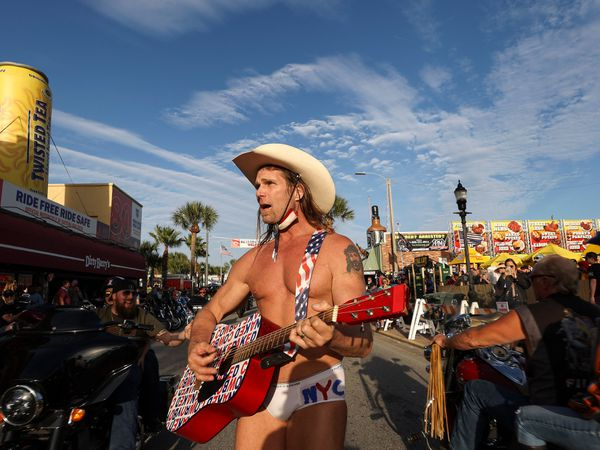 Robert Burck, better known as the Naked Cowboy, walks down the middle of Main Street while performing in Daytona, Florida