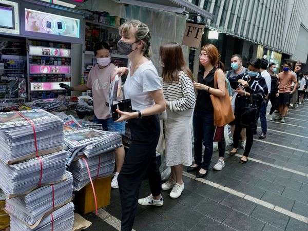 People queue up for last issue of Apple Daily at a newspaper booth at a downtown street in Hong Kong