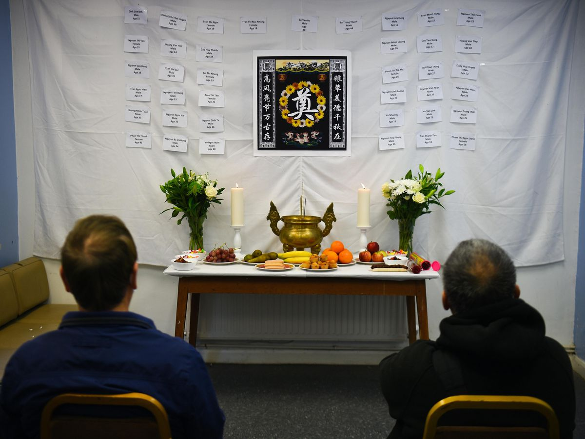 Visitors to the memorial shrine at the Hackney Chinese Community Services mark the first anniversary of the Essex container tragedy