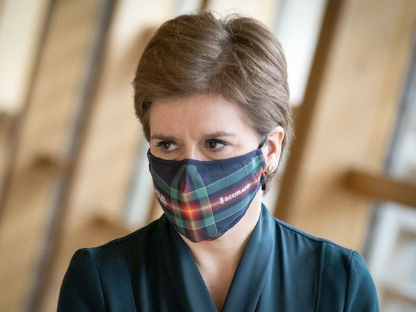Nicola Sturgeon walking into the chamber at Holyrood while wearing a face mask