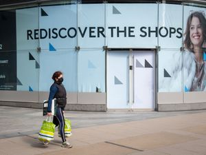 A woman walks past a 'Rediscover the shops' poster