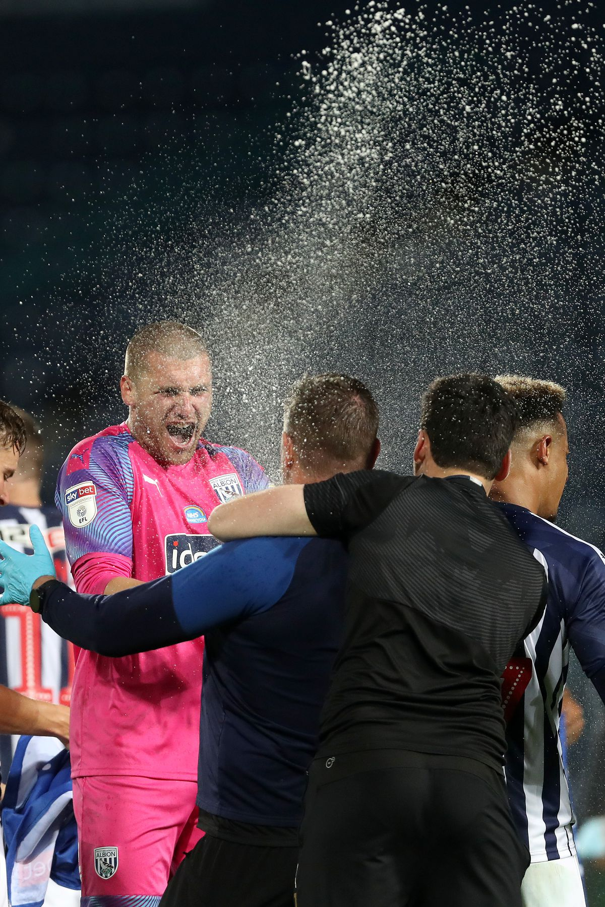 Sam Johnstone of West Bromwich Albion sprays champagne as he celebrates promotion to the Premier League on the pitch at the end of the match. (AMA)