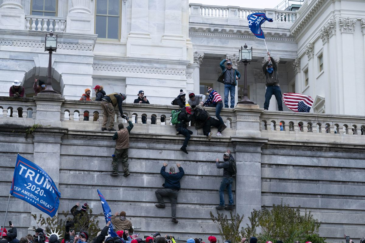 Supporters of President Donald Trump climb the west wall of the the U.S. Capitol on Wednesday, Jan. 6, 2021, in Washington. (AP Photo/Jose Luis Magana).
