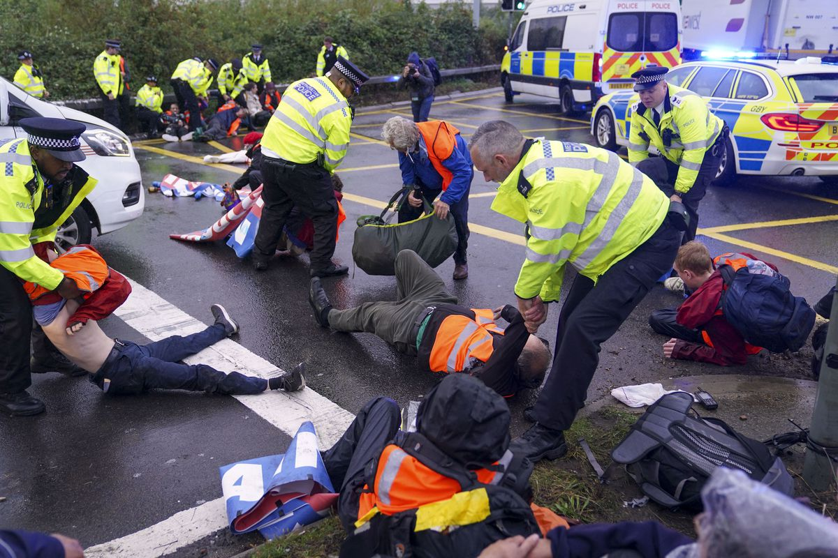Police officers move Insulate Britain protesters occupying a roundabout leading from the M25 motorway to Heathrow Airport