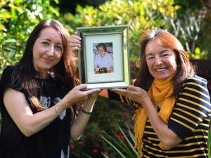 Julie Robson and her sister Chris Hammond, holding a photograph of their mother Brenda Walker
