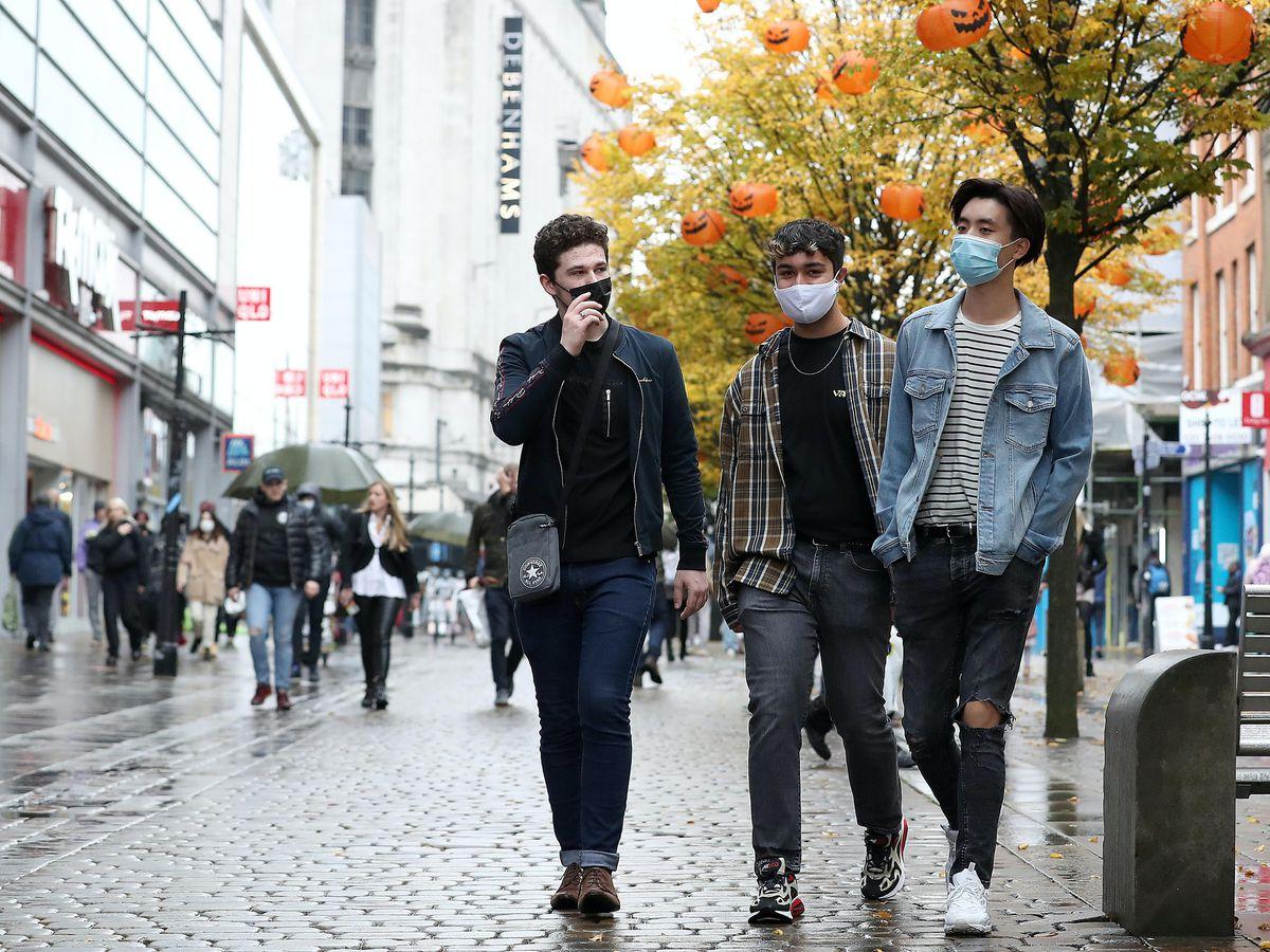 People wearing face masks walk down Market Street in Manchester