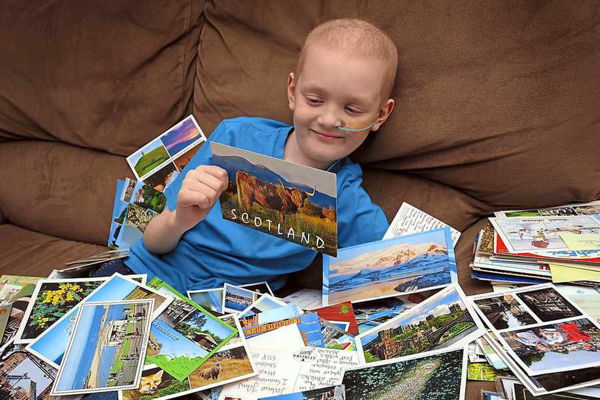 Joshua surrounded by some of his well wishing postcards that have flooded in from people around the globe.