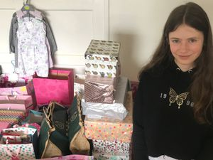 Honor Sutton, with some of the 67 gift-filled boxes and bags she created