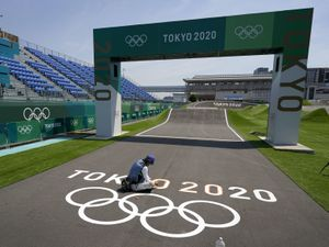 A worker paints Olympic rings at the finish line of the BMX racing track as preparations continue for the 2020 Summer Olympics