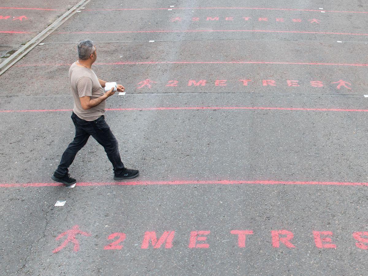 People walk over two metre social distancing markings