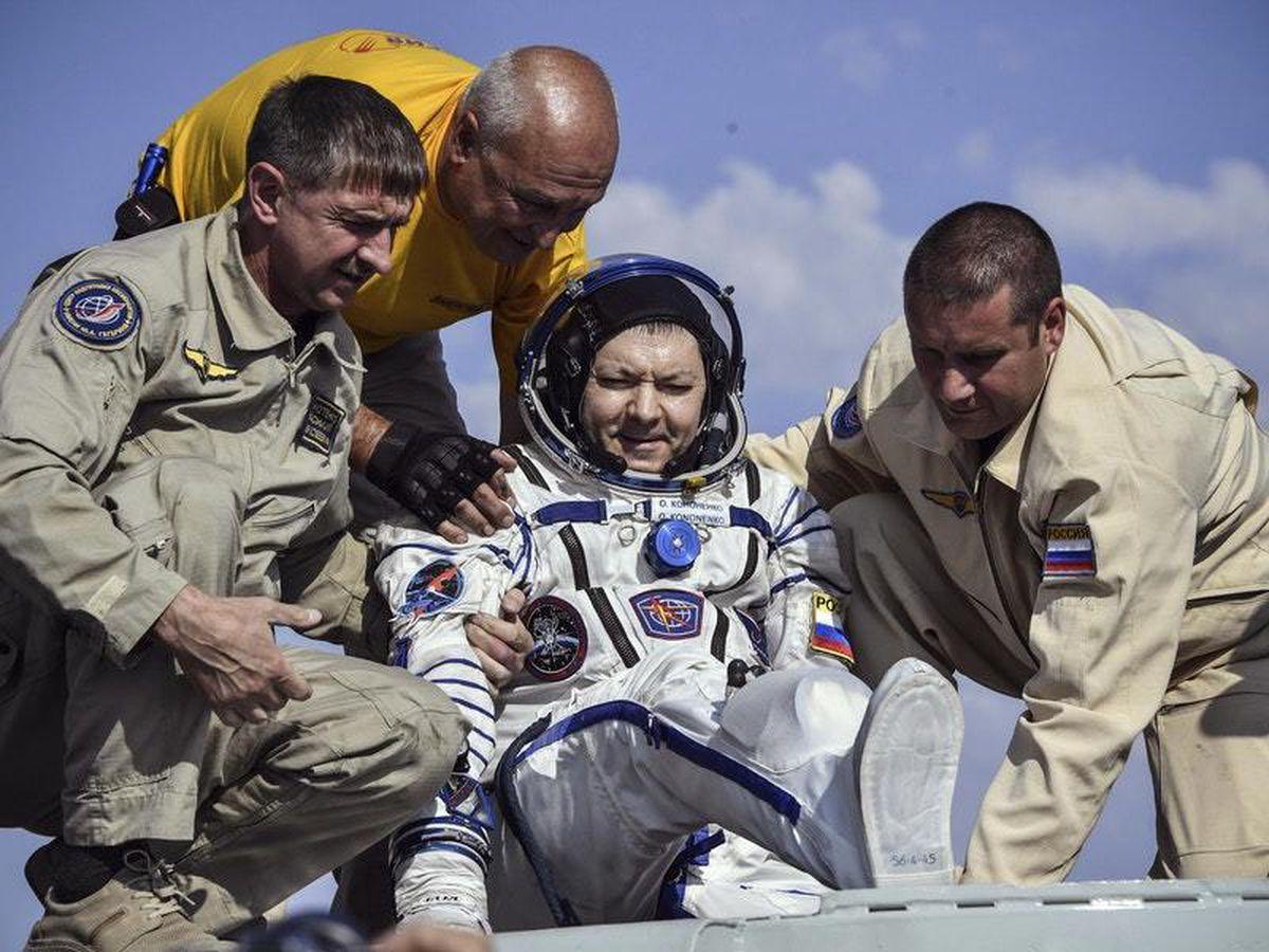 A rescue team helps Russian cosmonaut Оleg Kononenko