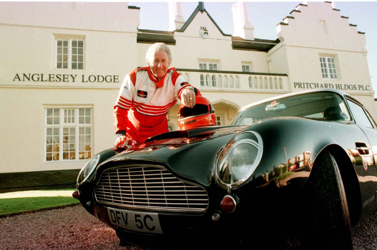 Fred in racing gear with his Aston Martin
