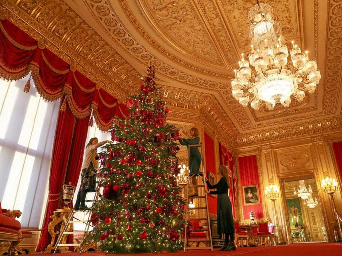 Royal Collection Trust staff put the finishing touches to a 15ft Christmas tree in the Crimson Drawing Room at Windsor Castle