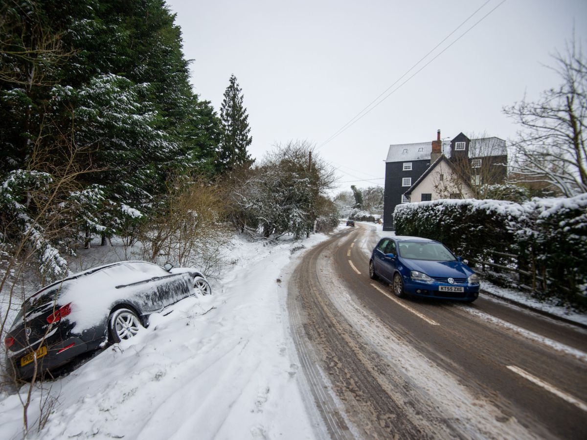 Abandoned cars in a snow-filled ditch in Needham Market in Suffolk