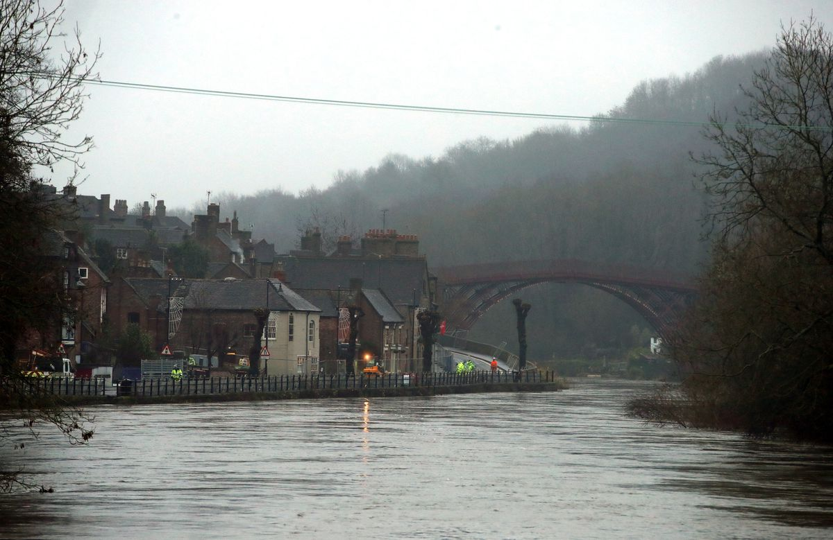 Environment Agency personnel place flood barriers on a bank of the high River Severn, near Ironbridge