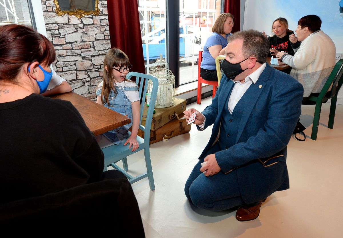 Magician Ian Brennan surprises Sofie Dudey, aged 7, from Wednesbury