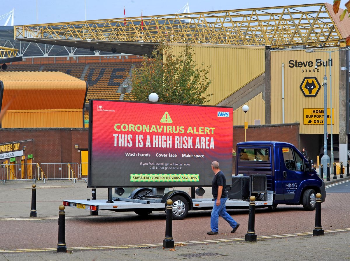 Illuminated signs warn residents to the dangers of coronavirus. Here Pete Brittain checks on a sign outside Molineux.