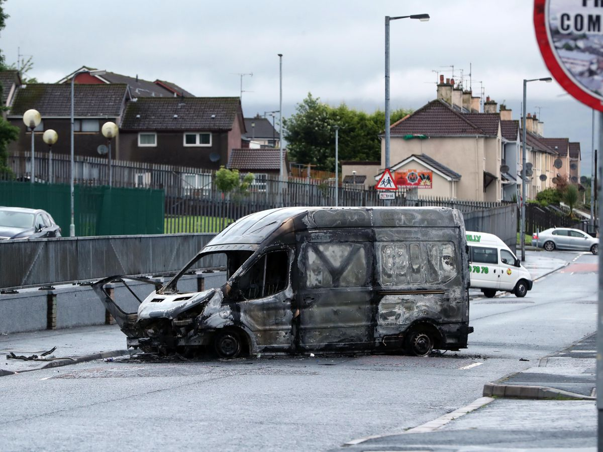 A burnt-out van in the Creggan area of Londonderry as the coffin of John Hume is taken to St Eugene's Cathedral ahead of his funeral