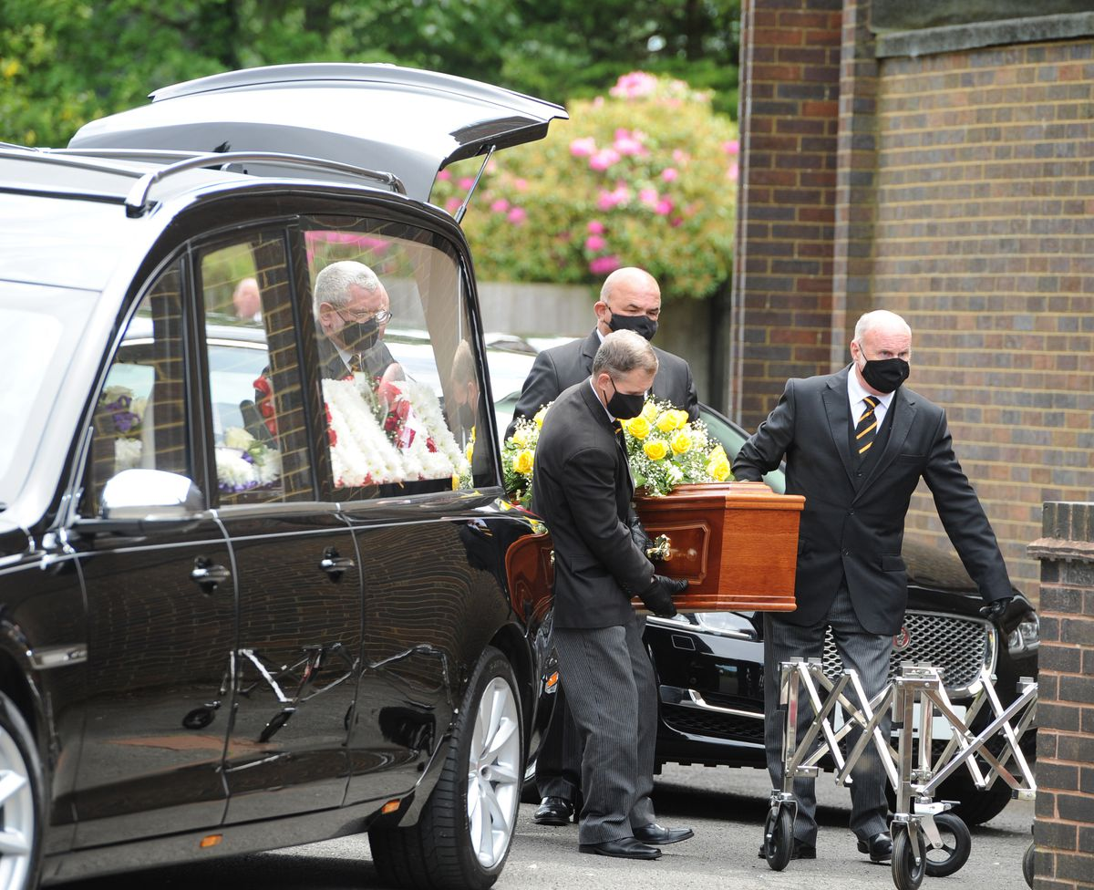 The coffin of Tony McGinn is taken from the hearse, ready for the service