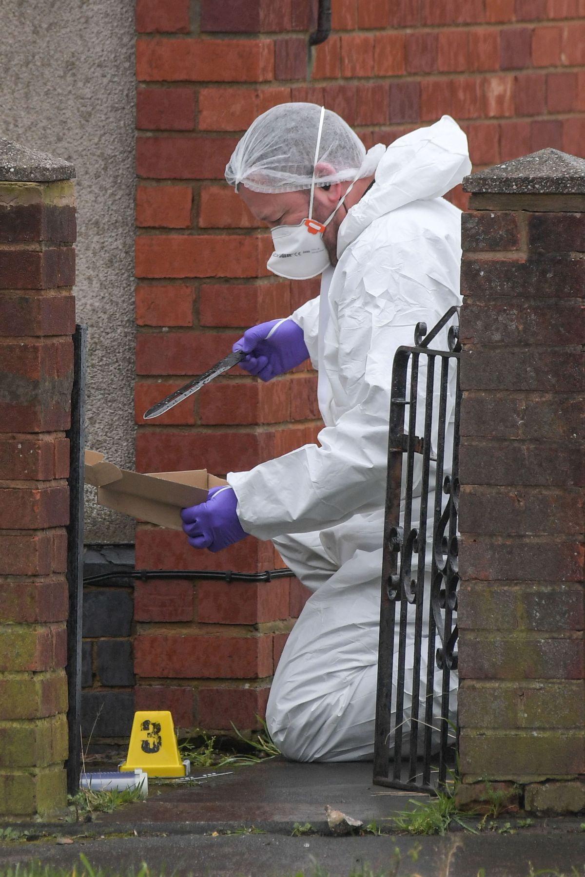 A forensic officer recovers a blade on Pensnett Road. Photo: SnapperSK