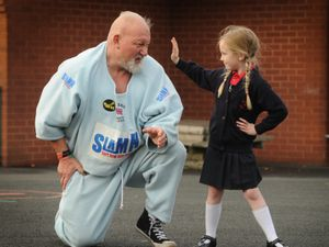 Strongman 'Big Dave' Gauder, of Birmingham, shows pupils how to stand up to bullies, including pupil Harley Mason, aged 4, at St Joseph's primary school, Darlaston.