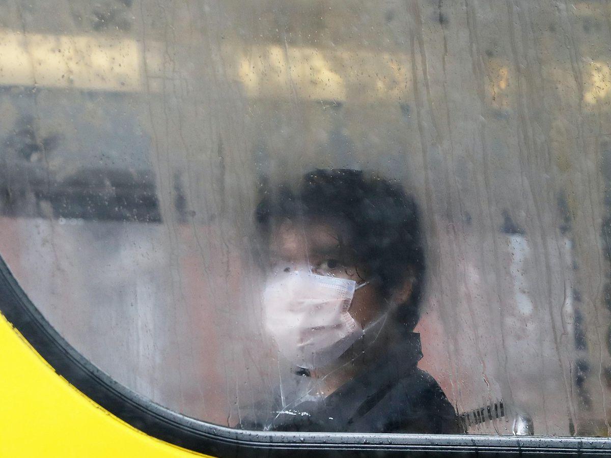 A bus passenger wears a face mask