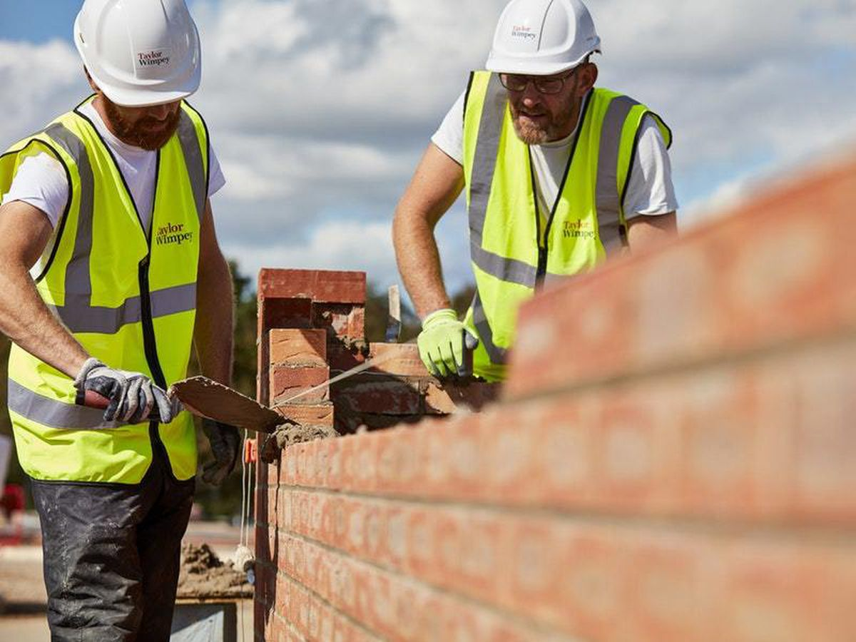 Two construction workers building a wall