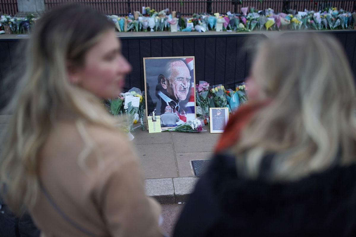 People look at flowers left outside Buckingham Palace, London, following the announcement of the death of the Duke of Edinburgh at the age of 99.