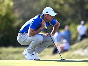 Rory McIlroy crouches to consider a putt