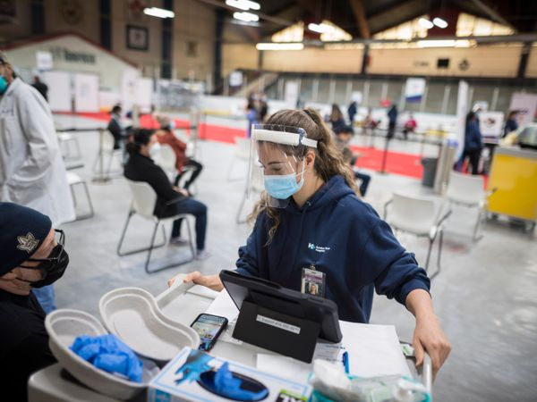 A nurse in mask and visor prepares to administer a Covid-19 vaccine to a man