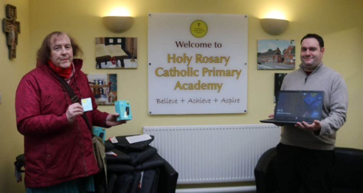 Councillor Anwen Muston, left, delivering the digital equipment to Holy Rosary principal Adam Jewkes
